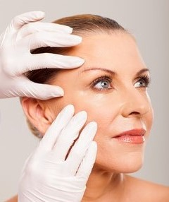 doctor doing skin check on mid age woman face over white background